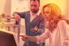 Neugieriger CEO und ihr Assistent, die den Bericht auf Fehlern überprüft stockbilder