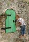 Neugieriger Junge, der an der Tür späht stockfoto