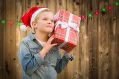 Neugieriger Junge, der Santa Hat Holding Christmas Gift auf Holz trägt lizenzfreie stockfotos
