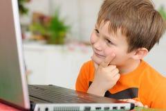 Neugieriger Junge mit Computer stockfoto