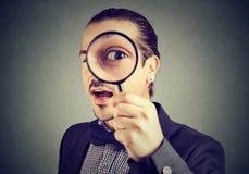 Neugieriger junger Geschäftsmann, der durch eine Lupe schaut lizenzfreie stockbilder