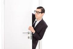 Neugieriger junger Geschäftsmann, der durch eine Tür schaut Lizenzfreie Stockfotografie