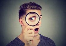 Neugieriger junger Mann, der durch eine Lupe schaut Lizenzfreies Stockfoto