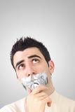 Neugieriger junger Mann, der graues Kanalband auf Mund hat Lizenzfreie Stockfotos