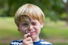 Neugieriger kleiner Junge, der durch Lupe schaut Stockfotografie