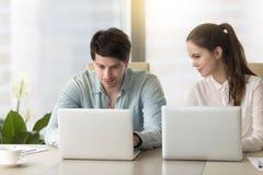 Neugieriger weiblicher ausspionierender männlicher Kollege, arbeitend an Laptop, sneakin lizenzfreies stockfoto