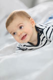 Neugieriges Baby, das auf Bett liegt Lizenzfreie Stockfotos
