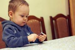 Neugieriges Baby, das mit Abgleichungen spielt Stockbild
