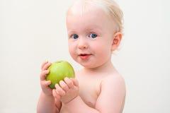 Neugieriges blondes Baby, das Apfel isst Stockbilder