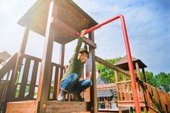 Neugieriges furchtloses kleines Mädchen, das auf Spielplatz allein im sonnigen Wetter klettert Stockbild