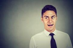Neugieriges junges Geschäftsmannhören Stockbilder