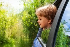 Neugieriges Kind, das außerhalb des Autofensters schaut Stockfotos