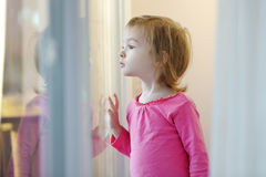 Neugieriges Kind, das aus dem Fenster heraus schaut Lizenzfreie Stockbilder