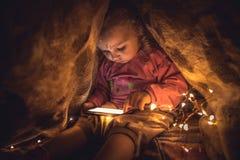 Neugieriges Kind, das mit dem intelligenten Telefon sich versteckt im geheimen Ort spielt Stockfotografie