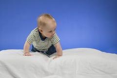 Neugieriges kleines Baby auf der weißen Decke, Atelieraufnahme, lokalisiert auf blauem Hintergrund Lizenzfreie Stockfotografie