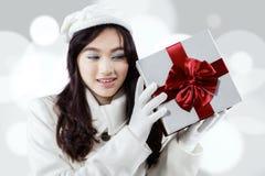 Neugieriges Mädchen, das eine Geschenkbox hält Lizenzfreie Stockfotos