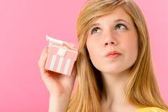 Neugieriges Mädchen, das ungeöffnetes Geschenk hält Lizenzfreie Stockfotografie