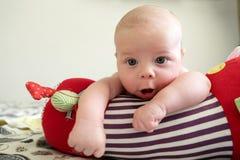 Neugieriges neugeborenes Baby, das auf einer kriechenden Rolle liegt Lizenzfreie Stockfotografie