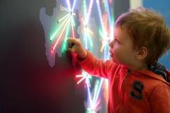 Neugierkind, das glühende Karte berührt stockfotografie