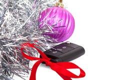 Neujahrsgeschenk mit dem Autoschlüssel und rotem Bogen lokalisiert Stockbild