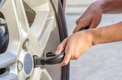 Neumático cambiante con la llave de la rueda Fotografía de archivo