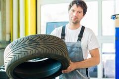 Neumático cambiante del mecánico de automóviles en taller imagen de archivo