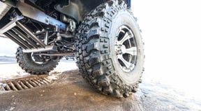 Neumático de coche con el primer campo a través del modelo en el camino Foto de archivo libre de regalías
