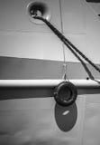 Neumático de coche que cuelga del lado de la nave Fotos de archivo