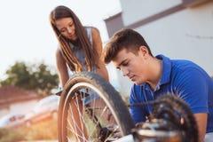 Neumático de la reparación del muchacho del adolescente en la bicicleta Fotos de archivo libres de regalías