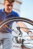 Neumático de la reparación del muchacho del adolescente en la bicicleta Imagenes de archivo