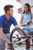 Neumático de la reparación del muchacho del adolescente en la bicicleta Foto de archivo
