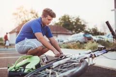 Neumático de la reparación del muchacho del adolescente en la bicicleta Imagen de archivo