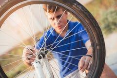 Neumático de la reparación del muchacho del adolescente en la bicicleta Fotografía de archivo