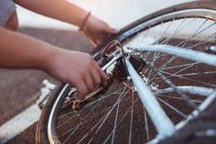 Neumático de la reparación del muchacho del adolescente en la bicicleta, cierre para arriba Fotos de archivo