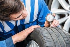 Neumático de Pressing Gauge Into del mecánico en garaje Fotografía de archivo