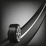 Neumático del coche en el camino aislado sobre fondo negro Foto de archivo