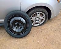Neumático desinflado al lado de un repuesto listo para ser montado foto de archivo