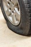 Neumático desinflado de la rueda de coche en el camino Imágenes de archivo libres de regalías