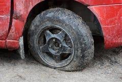 Neumático desinflado negro de un coche rojo en un camino de tierra foto de archivo libre de regalías