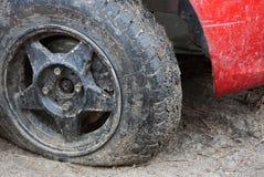 Neumático desinflado negro de un coche rojo en un camino de tierra imagenes de archivo