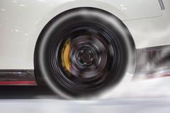 Neumático trasero ardiente del coche deportivo para calentar para arriba el caucho para la buena tracción antes de comienzo para  imagen de archivo libre de regalías