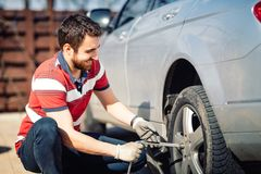Neumáticos cambiantes sonrientes del hombre y del mecánico, usando el enchufe y la llave de la rueda fotografía de archivo libre de regalías