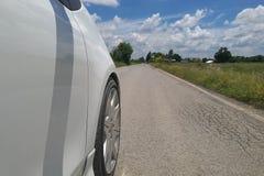 Neumáticos de coche en el camino de la mezcla en el campo Foto de archivo