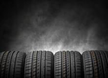 Neumáticos de coche en un fondo oscuro Fotografía de archivo libre de regalías