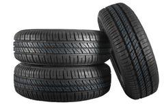 Neumáticos de coche nuevos e inusitados contra fondo aislado Fotos de archivo