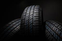 Neumáticos de coche nuevos e inusitados contra fondo oscuro Fotos de archivo libres de regalías