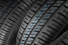 Neumáticos de coche nuevos e inusitados contra fondo oscuro Imagen de archivo