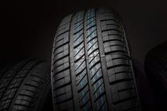 Neumáticos de coche nuevos e inusitados contra fondo oscuro Fotografía de archivo libre de regalías