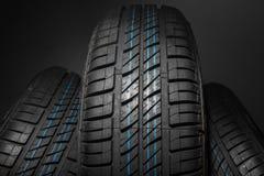 Neumáticos de coche nuevos e inusitados contra fondo oscuro Imagenes de archivo