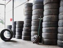 Neumáticos de coche usado apilados en pilas en el depósito de chatarra Ruedas viejas que reciclan y concepr de la utilización foto de archivo libre de regalías